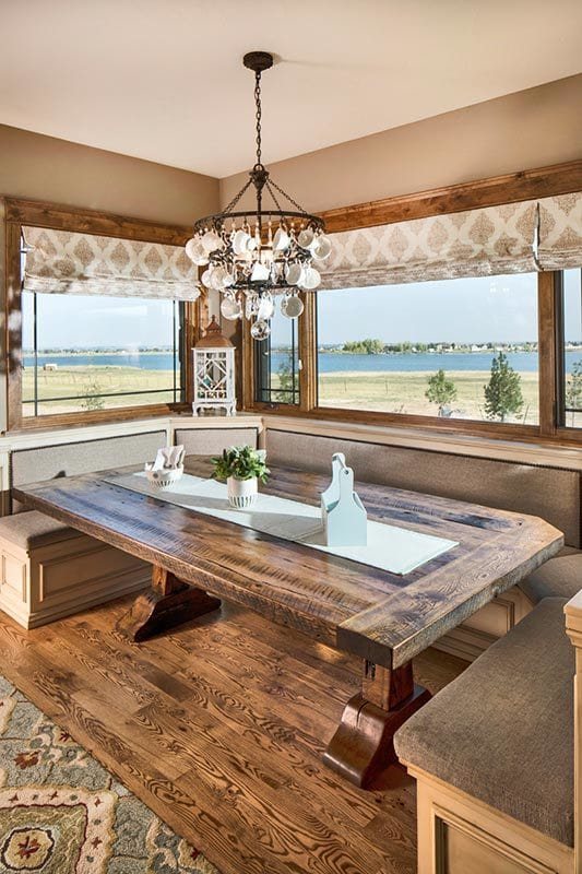 A breakfast nook offering a built-in seat and a rustic dining table under the wrought iron chandelier.
