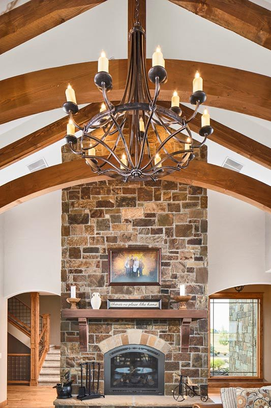 An oversized candle chandelier hanging from the beamed ceiling complements well with the stone fireplace.
