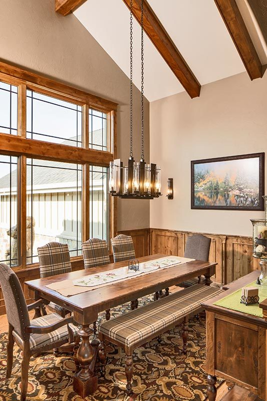 The dining room has a glass chandelier and a rectangular dining table surrounded by checkered chairs and a matching bench.