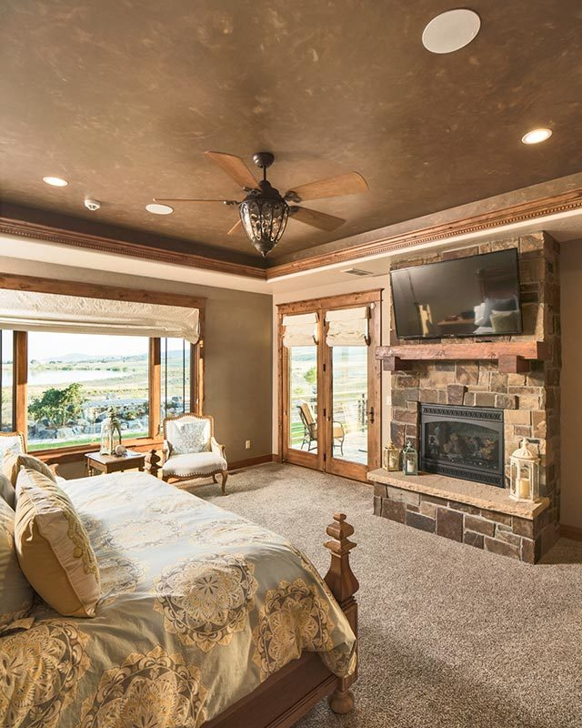 Primary bedroom with a wall-mounted TV, a stone fireplace, a sitting area, and a double door that leads out to the rear deck.
