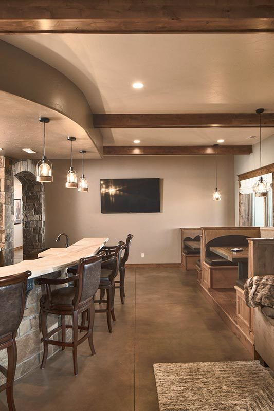 Recreation room with multiple sitting areas and a curved wet bar illuminated with glass pendants.