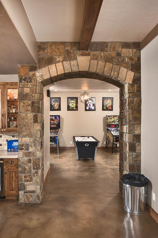 A brick archway opens to the game room adorned with framed artworks.
