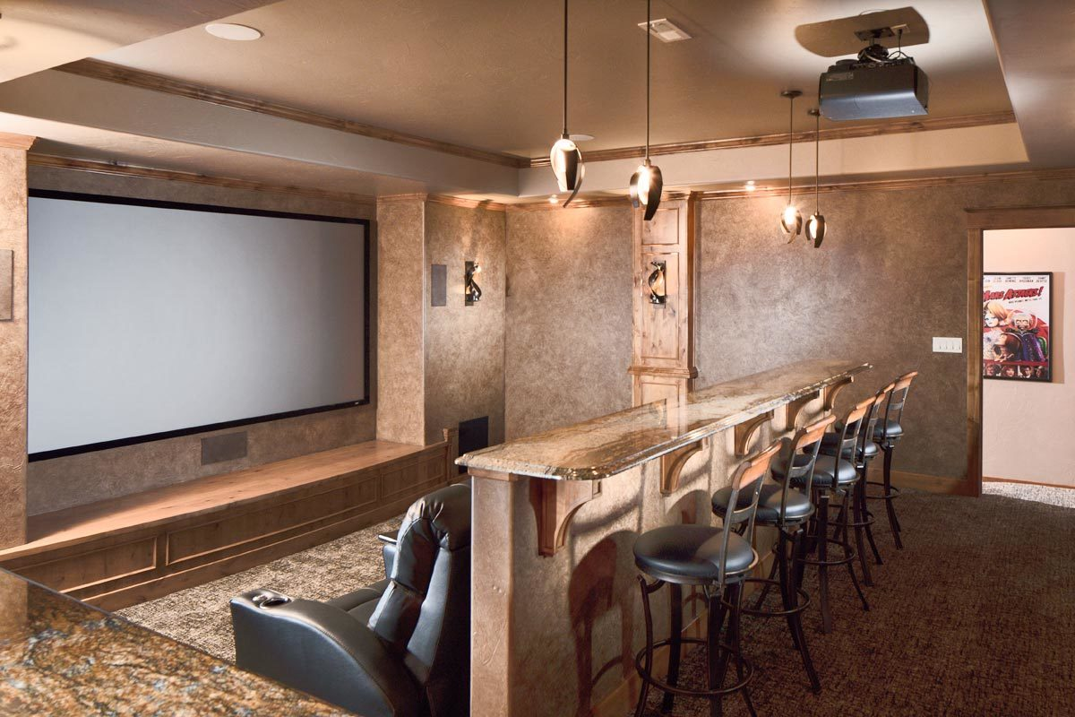 Cozy home theater with black recliners and a granite top bar lined with round bar stools.