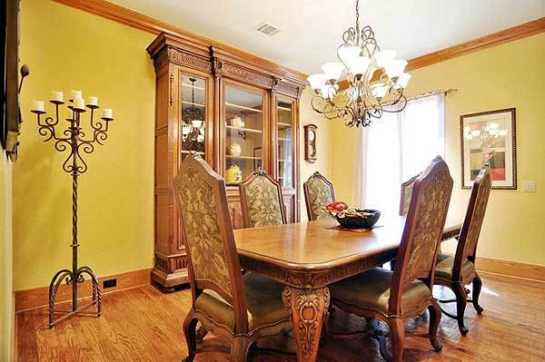 Formal dining room with a rectangular dining set, a china cabinet, and a wrought iron floor candelabra matching with the ornate chandelier.
