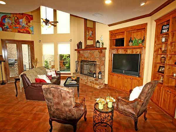 The family room has cozy seats, a stone fireplace, and wooden built-ins that blend in with the terracotta flooring.