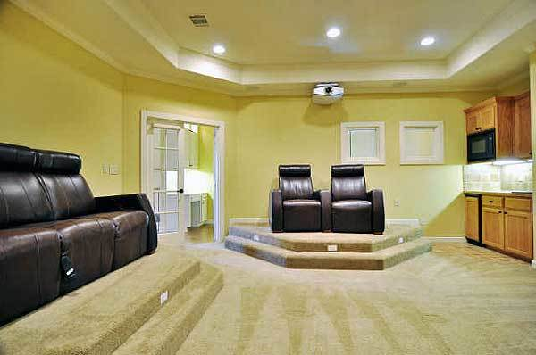 The home theater features a tray ceiling, a wet bar, and two-step platforms topped with leather recliners.