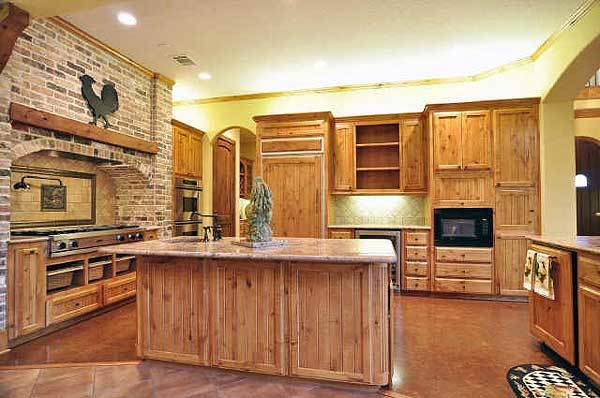 The kitchen offers natural wood cabinetry, a granite top island, and an arched cooking alcove clad in beautiful stone bricks.
