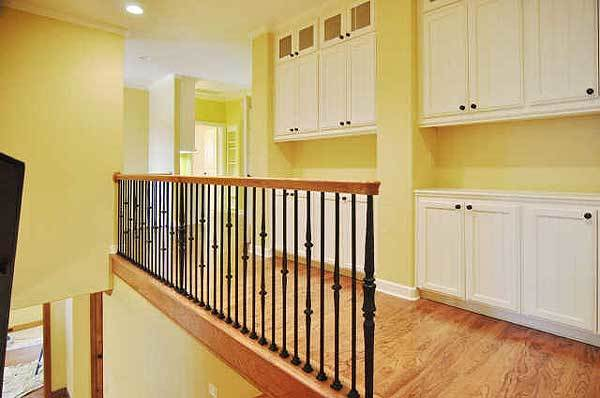 The second-floor balcony is filled with white built-in cabinets fixed against the yellow walls.