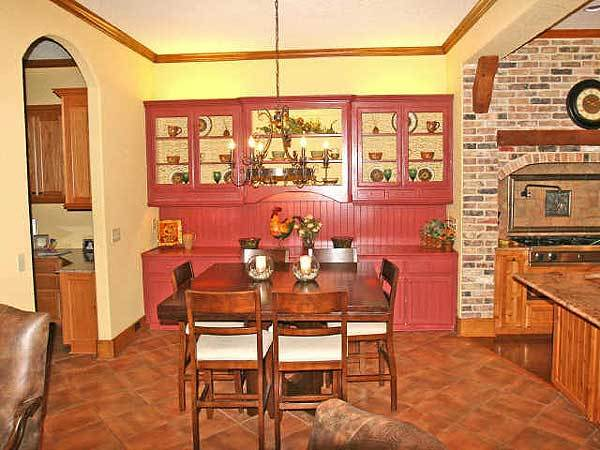 The breakfast nook offers a red buffet cabinet and a wooden dining set situated under the warm candle chandelier.