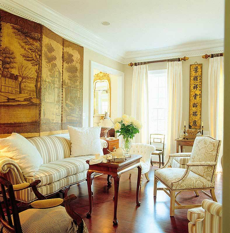 The family room offers upholstered chairs, a wooden coffee table, and a striped sofa under the three-panel artwork.