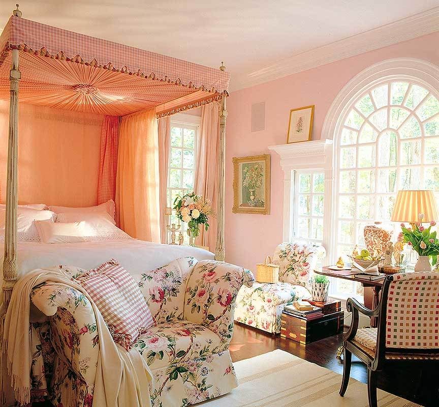Primary bedroom with a canopy bed, floral seats, and a large arched window that brings plenty of natural light in.