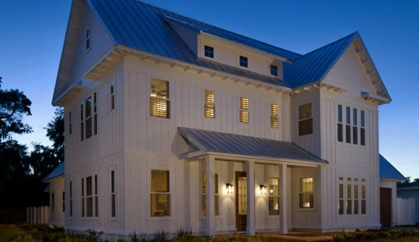 Night view of the home facade well-lit by warm, ambient light from the interior and the outdoor sconces.