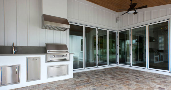 Covered porch with an outdoor kitchen fixed against the white beadboard walls.