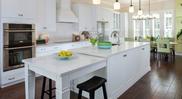 Eat-in kitchen with white cabinets, stainless steel appliances, and a center island incorporated with a snack bar.
