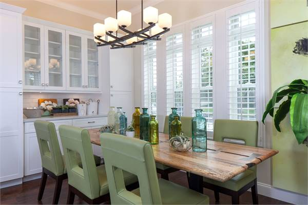 The dining room offers a white buffet cabinet, green upholstered chairs, and a rectangular table topped with multi-colored transparent bottles.