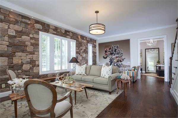 The living room offers a gray sectional sofa, stump tables, and round back armchairs sitting on a floral area rug.