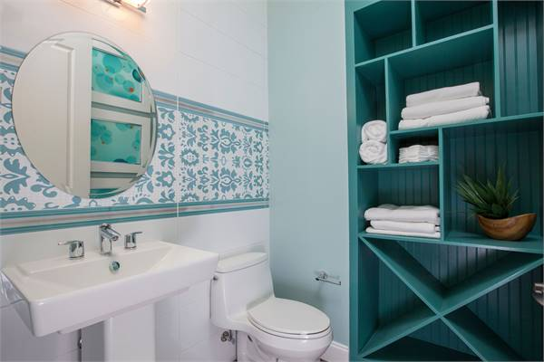 Bathroom with green beadboard shelving, a toilet, and a pedestal sink paired with a round mirror.