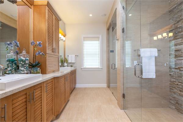 The primary bathroom is equipped with a large walk-in shower and wooden vanity with dual vessel sinks.