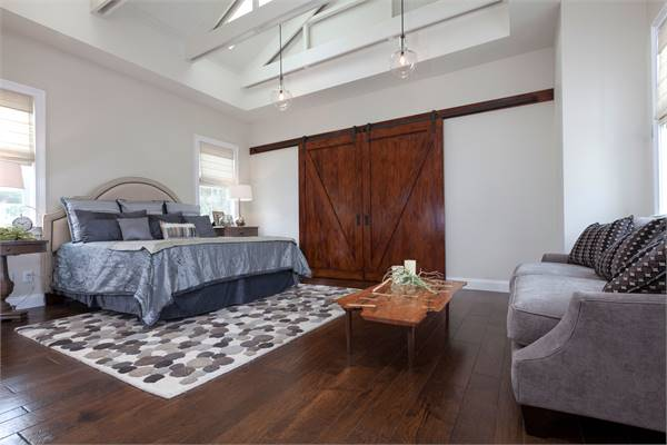 Primary bedroom with a beamed ceiling and a large barn door that blends in with the dark hardwood flooring.