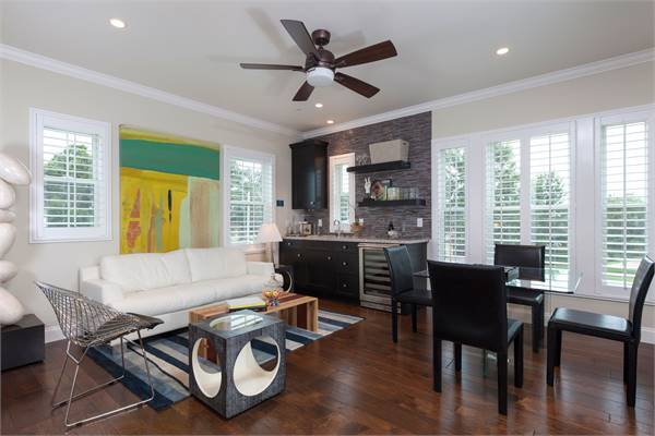 The activity room is filled with various seats, a glass dining set, and a wet bar situated in between the louvered windows.