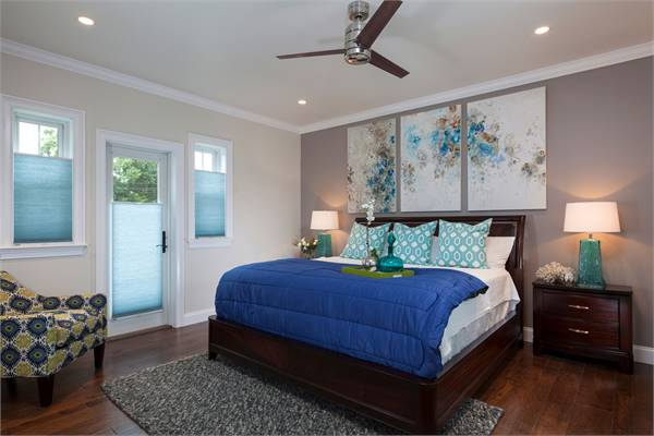 This bedroom has wide plank flooring and gray walls adorned with a multi-panel artwork.