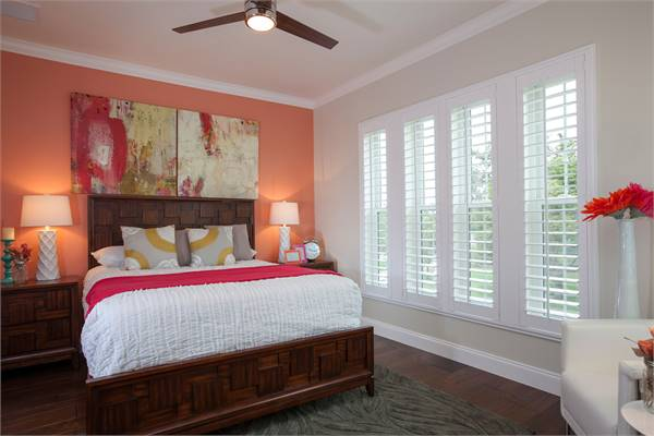 This bedroom features a carved wooden bed flanked with matching nightstands and sleek table lamps.