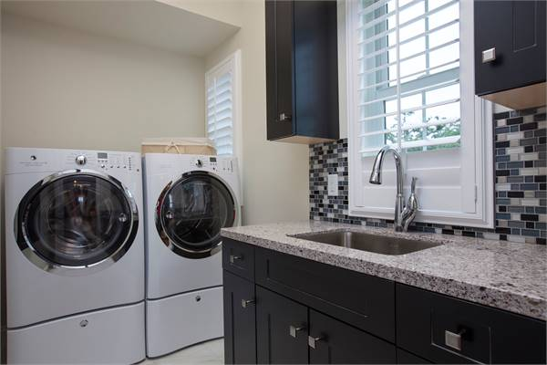 Laundry room with white front-load appliances and a granite top counter with sink accentuated with a striking linear mosaic tile backsplash.