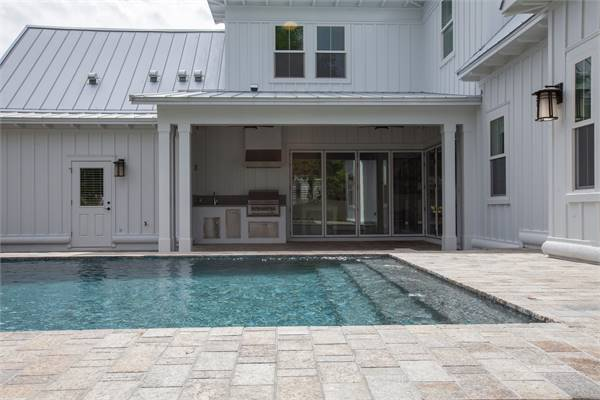 Covered lanai with an outdoor kitchen and an in-ground pool surrounded with brick paving.