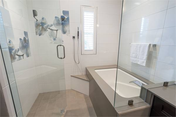 A glass hinged door opens to the shower area combined with a deep soaking tub.