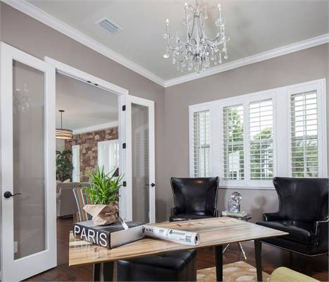 The study has black leather armchairs and a wooden desk illuminated with a fancy crystal chandelier.