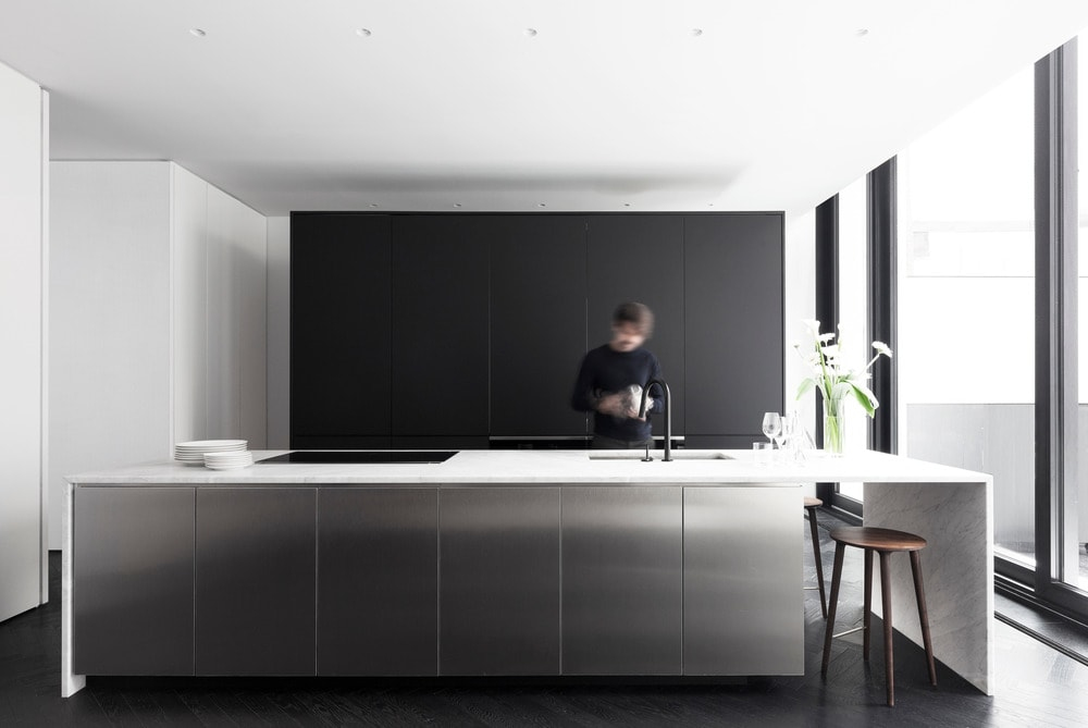This is the gorgeous and simple modern kitchen with a large silver kitchen island paired with a large modern structure with black panels across from the island. This stands out against the bright white ceiling and walls.