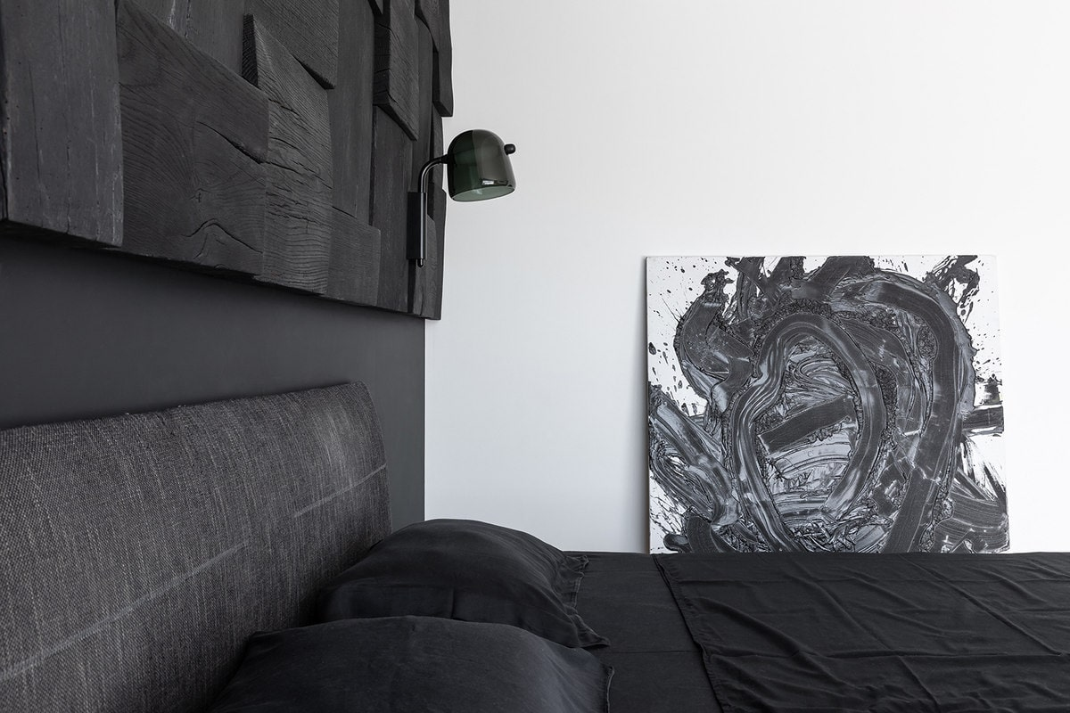 The side of the bed has a white wall that is adorned with a charming black and white artwork that is leaning against the wall.
