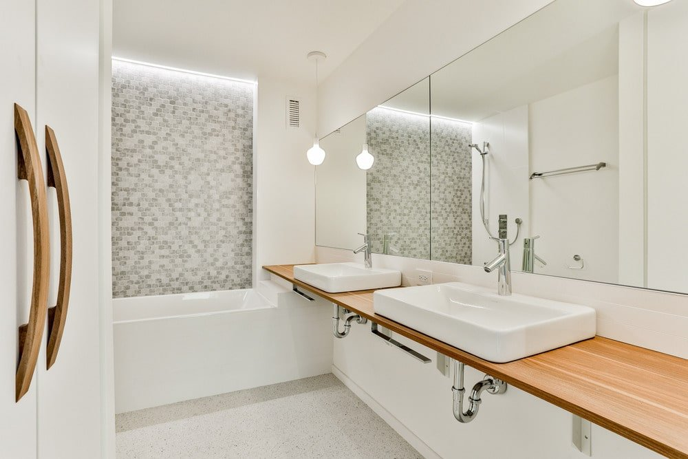 The bright and white bathroom has a wooden floating vanity that supports a couple of porcelain sinks topped with wall-mounted mirrors and pendant lights from the white ceiling.