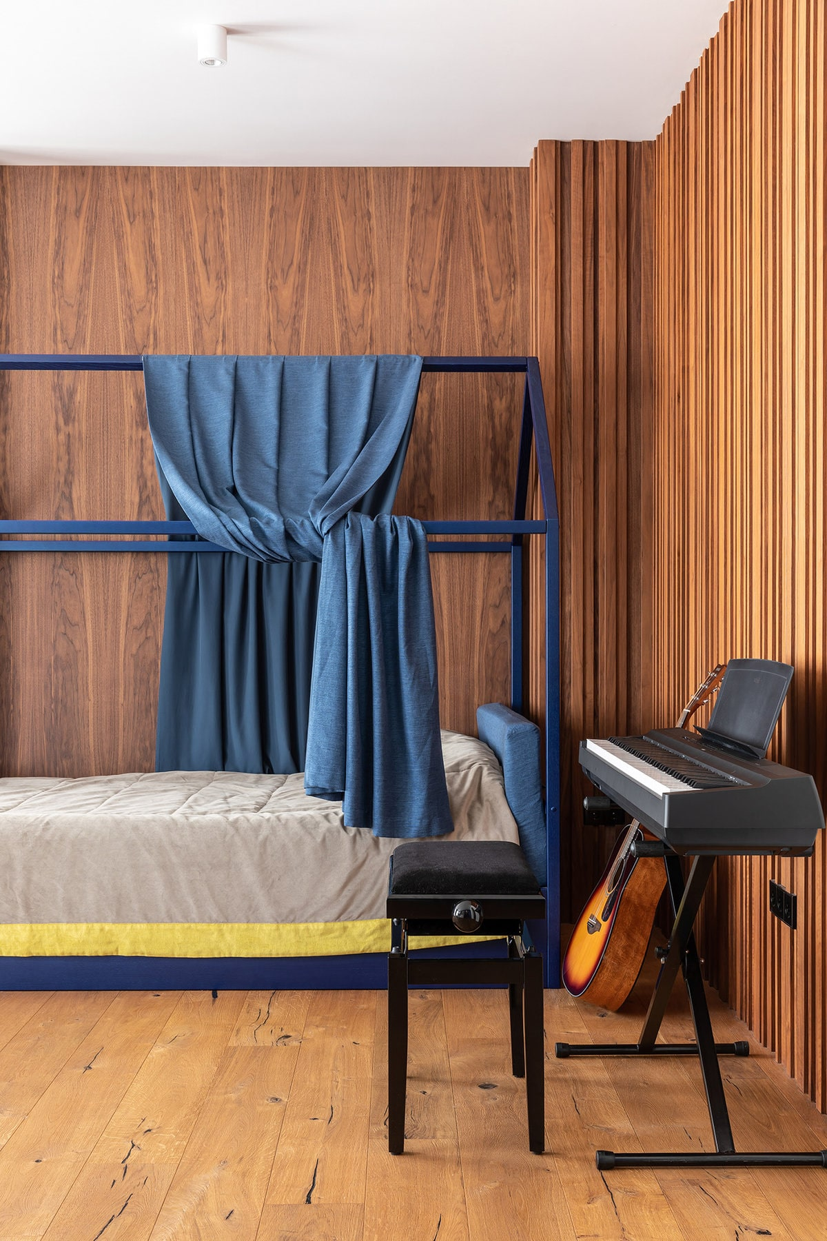 There is also a small music area at the side of the bed with a guitar and a propped up keyboard paired with a black stool.