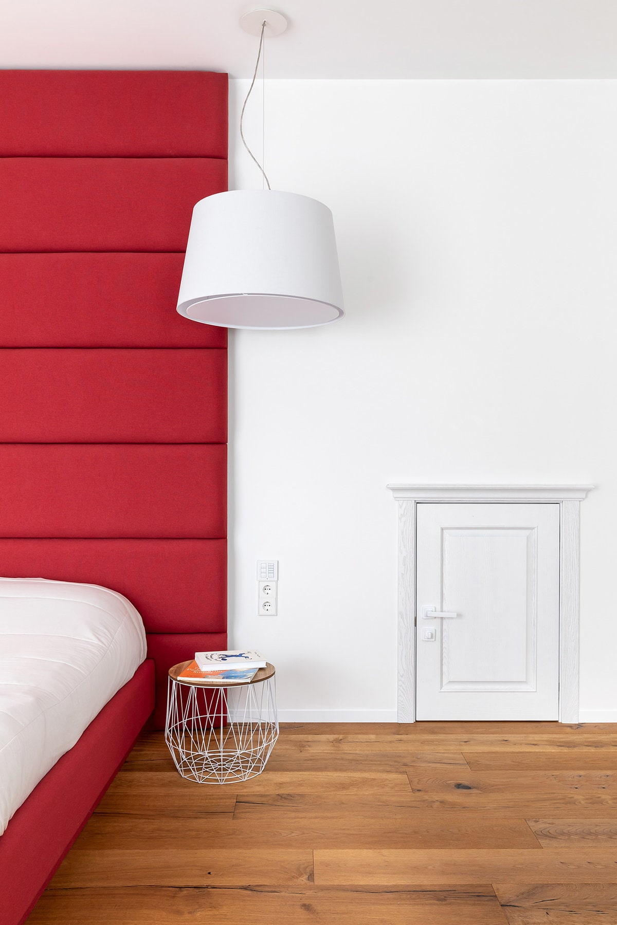 A close look at the bed shows the large red cushioned headboard and a small round bedside table topped with a large white pendant light.