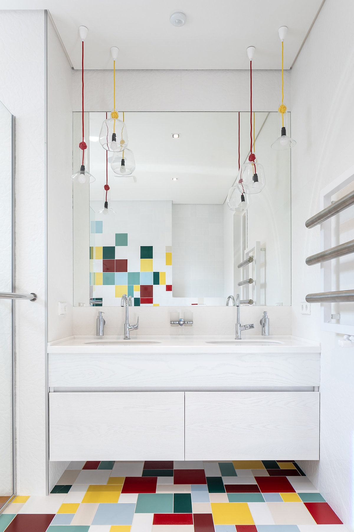 This is a quirky and fun bathroom with white walls, a white ceiling and a modern white vanity. These are complemented by the colorful tiles of the floor and the pendant light by the wall-mounted mirror.