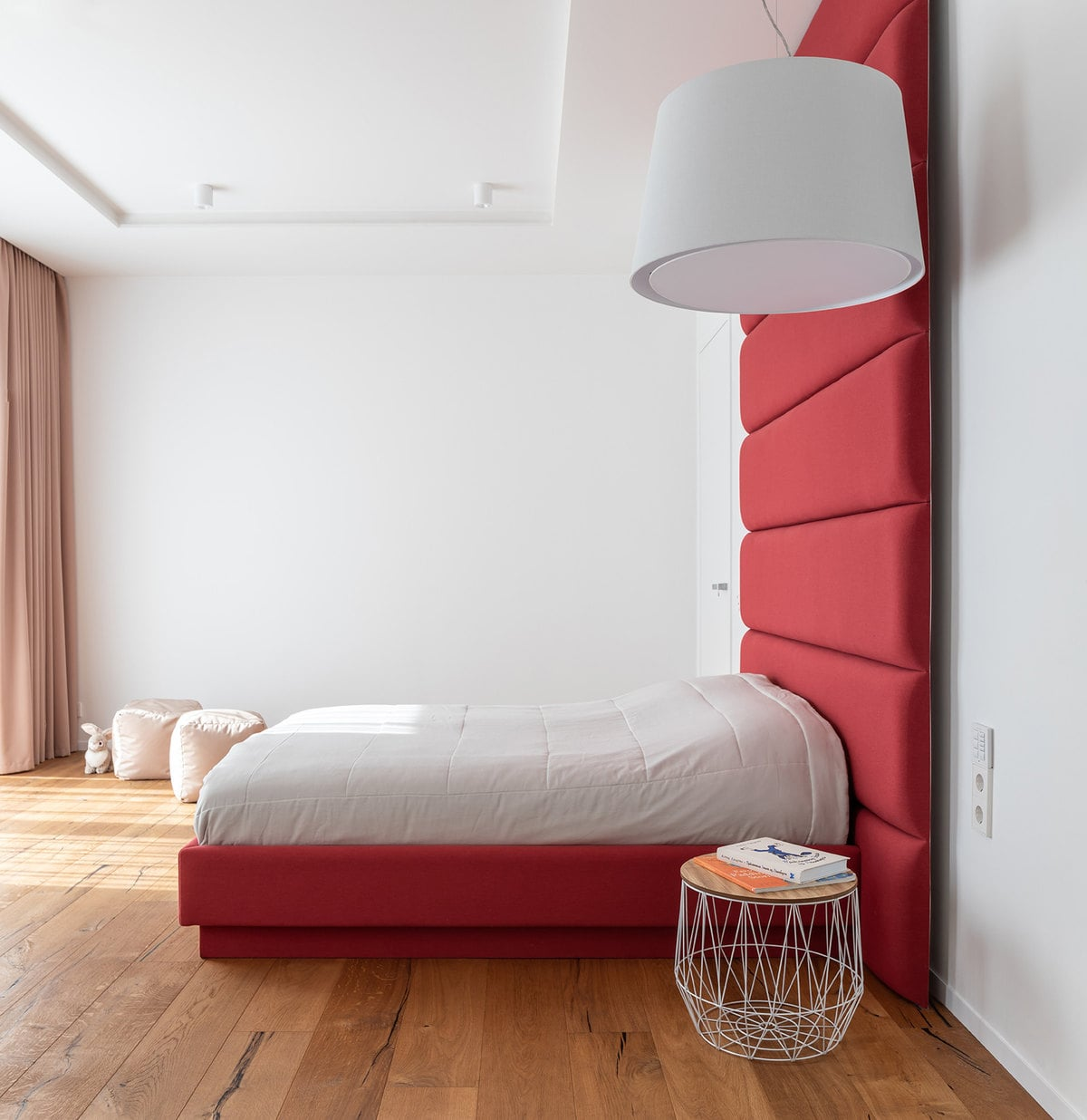 This other bedroom has white walls and white ceiling to make the red structures of the stand out. The red patform bed also stands out against the hardwood flooring.