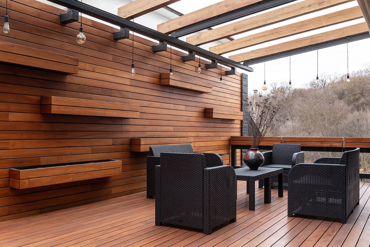 The black outdoor furniture of this patio stands out against the wooden flooring and walls with floating planters awaiting for the adornment of plants.