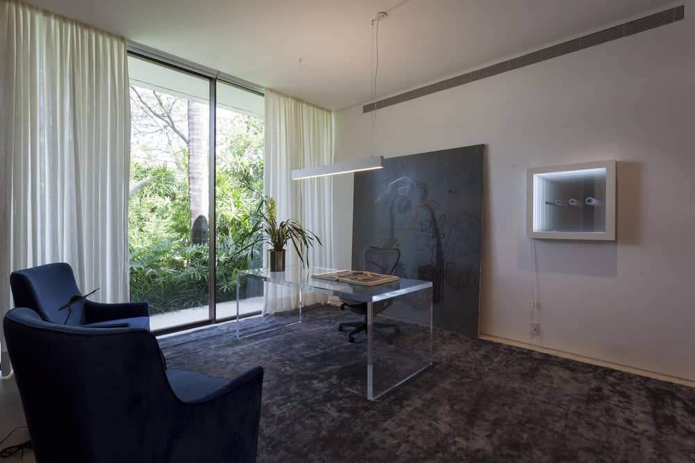 This is a sophisticated modern home with a transparent desk. This pairs quite well with the black carpeting and black wall artwork behind the black swivel chair that stands out against the white walls and ceiling.