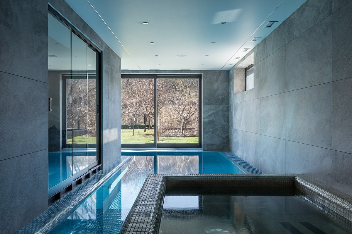 This indoor swimming pool also has a small jacuzzi-type pool at the cornerbordered with the same material as the wall illuminated by the natural lights.
