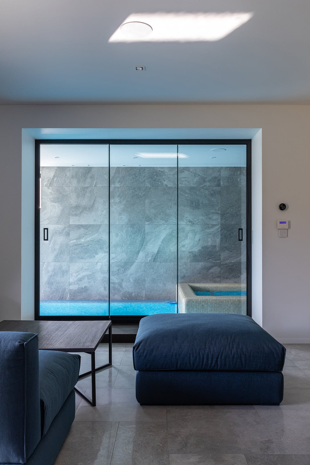 There is a lovely and comfortable living room area beside the indoor pool through the glass doors. It has a comfortable set of sofas in dark tones to contrast the white walls.