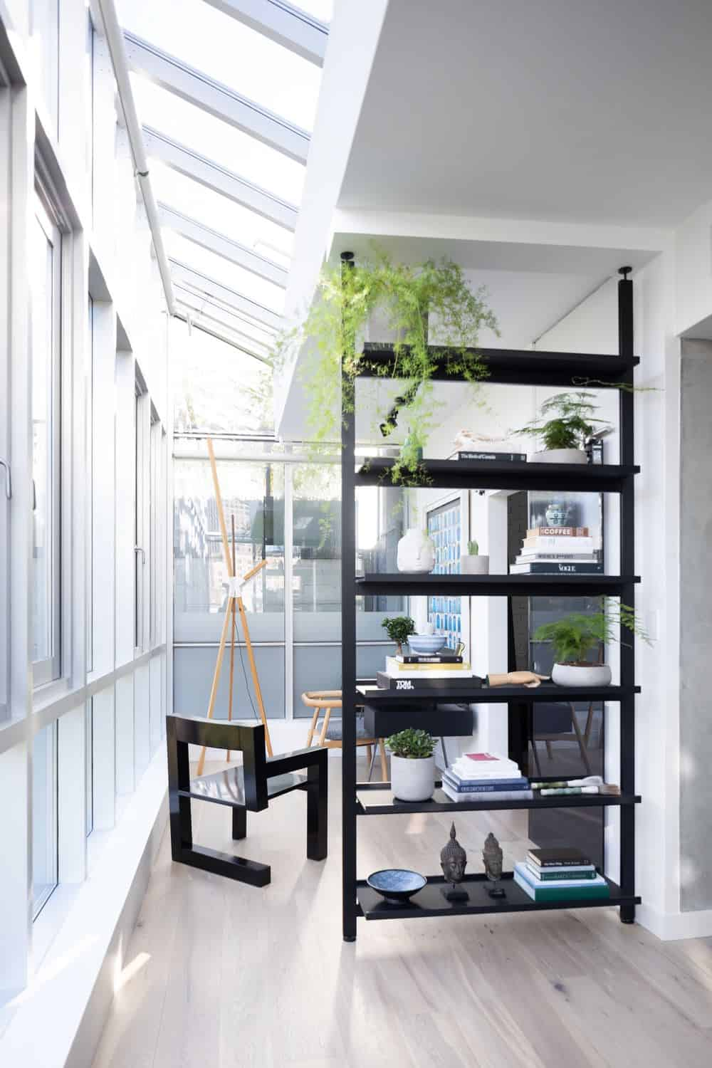 This is a small corner office that makes up for its small floor space with glass walls and skylights. This brightens the white half-ceiling and white wall to be contrasted by the black desk, chairs and shelves.