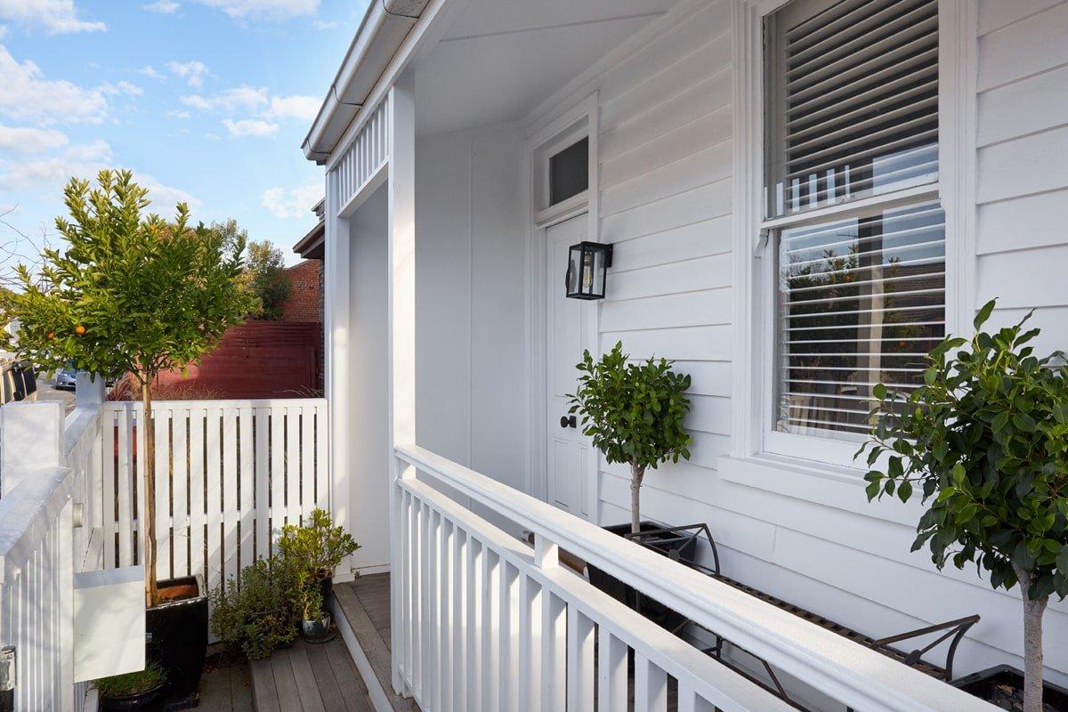 This is a close look at the small and cozy front porch. It has a wrought-iron bench flanked by potted plants under the window. Here you can also see the wall-mounted lamp of the main door.