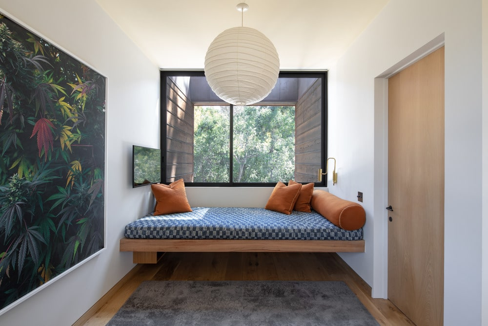 This is a charming and comfortable reading nook with a built-in wooden floating daybed with a cushion under the window. This is adorned with a large wall-mounted painting and a spherical pendant light.