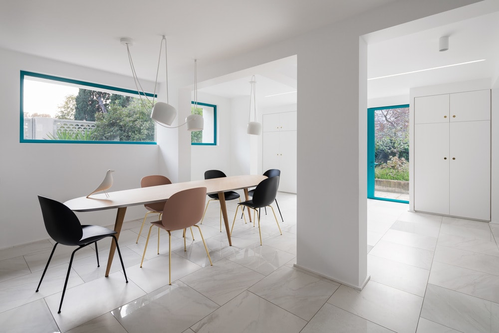 Next to the living room is the dining area with a long wooden dining table paired withmodern chairs that stand out against the white flooring tiles, walls and ceiling. There is also a large white pillar that gives the area a unique and clinical look.