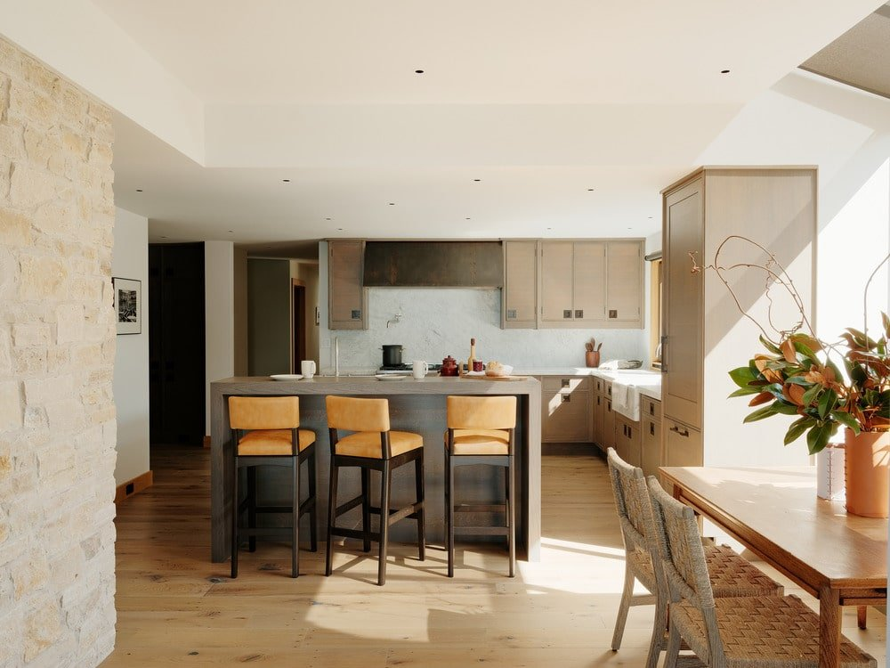 The kitchen has a breakfast bar attached to its kitchen island paired with beige stools that stand out against the light hardwood flooring. These pair well with the light wooden tone of the surrounding cabinetry with a white backsplash.