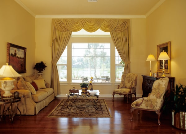 The living room has classy seats, rich hardwood flooring, and white framed windows dressed in elegant valances and curtains.