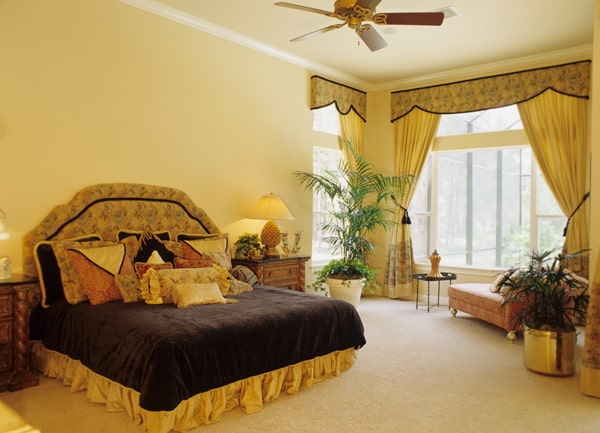 The primary bedroom features a classy upholstered bed and a comfy chaise lounge by the massive windows.