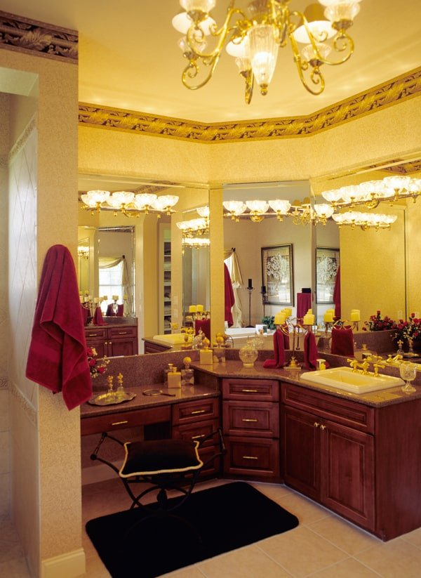 The primary bathroom is flooded with ambient lighting from the gilded chandelier and matching sconces fixed on top of the wooden vanity.