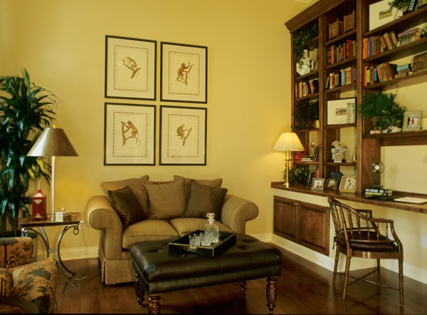 Den with dark wood built-ins, cozy sofas, hardwood flooring, and yellow walls adorned with animal artworks.